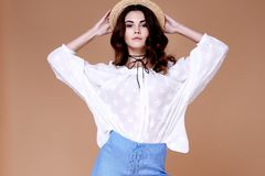 Sexy brunette woman wear short blue cotton short and silk summer. Collection blouse perfect body shape diet skin tan hold accessory hat glamour model fashion Stock Photo