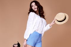 Sexy brunette woman wear short blue cotton short and silk summer. Collection blouse perfect body shape diet skin tan hold accessory hat glamour model fashion Stock Photos