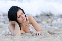 Sexy brunette woman, wear wet t-shirt as she lie on sandy beach. Gazing away, full length horizontal photo Royalty Free Stock Photo