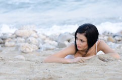 Sexy brunette woman, wear wet t-shirt as she lie on sandy beach. Gazing away, full length horizontal photo Royalty Free Stock Photos