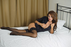Sexy brunette woman wearing black lingerie in bed Royalty Free Stock Image