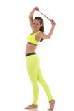 Sexy brunette woman wearing sports neon yellow bra and leggings stretching lateral trunk muscles with a use of sports rope. Stock Photography