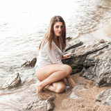 Sexy brunette woman in wet shirt sitting next to big rock at sea Stock Images