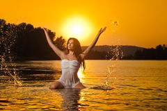 Sexy brunette woman in wet white lingerie posing in river water with sunset on background. Young female at the beach in twilight Stock Photos