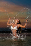 Sexy brunette woman in wet white swimsuit posing in river water with sunset sky on background. Young female playing with water Stock Images