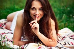 Sexy Brunette Woman With Brown Long Hair Style Showing Secret Sign Holding Finger Near The Mouth On Summer Grenn Grass Background Royalty Free Stock Photography