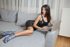 Free Sexy Brunette Young Woman Wearing Black Leather Short Dress Sitting On Bed And Watching On Laptop. Stock Photography - 150345272