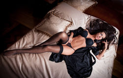 Sexy brunette young woman wearing black lingerie in bed Royalty Free Stock Photography