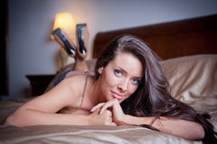 Sexy brunette young woman wearing black lingerie in bed Stock Image