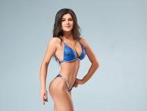 Sexy Brunettebodybuilderfrau im blauen Bikini Lizenzfreie Stockfotos