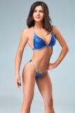Sexy Brunettebodybuilderfrau im blauen Bikini Stockfotografie