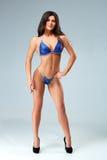 Sexy Brunettebodybuilderfrau im blauen Bikini Stockbilder