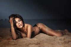 Sexy Brunettedame, die im Badeanzug aufwirft. Stockbild