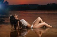 Sexy Brunettefrau in der Wäsche, die in Flusswasser legt Junge weibliche Entspannung auf dem Strand während des Sonnenuntergangs  Stockbilder
