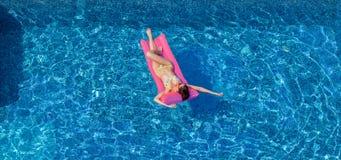 Sexy Brunettefrau, die auf rosa Matratze im Swimmingpool sich bräunt Stockbild