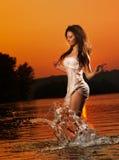 Brunettefrau im Badeanzug, der in Flusswasser läuft junge Frau, die mit Wasser während des Sonnenuntergangs spielt Schö Stockfoto