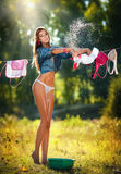 Sexy Brunettefrau im Bikini und in Hemd, die Kleidung setzen, um in der Sonne zu trocknen Stockfoto