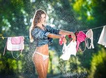 Sexy Brunettefrau im Bikini und in Hemd, die Kleidung setzen, um in der Sonne zu trocknen Sinnliche junge Frau mit den langen Bei Lizenzfreie Stockfotografie