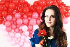 Sexy Brunettefrau mit roten Herzballonen und -blumen Stockfotos