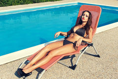 Brunettefrau sunbath am Swimmingpool Lizenzfreie Stockfotos