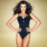 Sexy Brunettemädchen, das in der schwarzen Wäsche aufwirft Stockfotografie