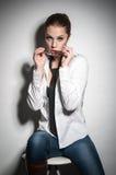 Sexy Brunettemädchen, das in einem Hemd im Studio aufwirft Stockfotos