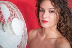 Sexy Brunettemädchen mit dem gelockten Haar mit Ventilator stockfotografie