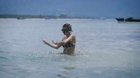 Sexy brunnete in black bikini dancing and splashing with water in the ocean on the beach of Bali island. Fit young girl stock video footage