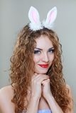 Sexy bunny girl. Beautiful young woman drinking Champagne white background Royalty Free Stock Image