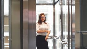 Sexy business lady in glasses uses the Elevator in the office building. stock video