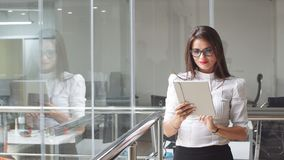 Sexy business lady in glasses uses a tablet in office building. Sexy business lady in glasses uses a tablet in office building Stock Photography