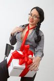Sexy business lady holding gift box with red ribbon sitting on chair Stock Image