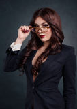 Sexy business woman in a dark business suit. Beautiful sexy secretary. On a dark background Royalty Free Stock Photography
