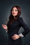 Sexy business woman in a dark business suit. Beautiful sexy secretary. On a dark background Royalty Free Stock Images