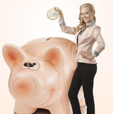Sexy business woman saving coin in money box. Blonde pretty business woman saving big coin and wearing elegant suit. Smiling and looking in camera Royalty Free Stock Photography