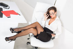 Sexy business woman. Sitting on office chair and using tablet pc Royalty Free Stock Image