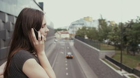 Sexy business woman using smartphone standing on a bridge overlooking the road, steadicam shot. slow mo stock footage