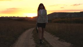 Sexy business woman walking along a country road with a briefcase in hand, the sun shimmers at sunset. Sexy business. Girl working in countryside. Beautiful stock video footage