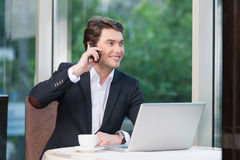 Sexy businessman talking by phone while drinking coffee. Royalty Free Stock Photos