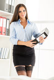 Sexy Businesswoman Holding A Binder. Young pretty businesswoman in a short skirt, holding a binder and smiling looking at the camera Royalty Free Stock Photography