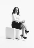 Sexy businesswoman sitting on white cube at studio Stock Photography