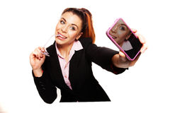Sexy businesswoman smiles for her self-portrait. Using a smart-phone isolated on a white background Royalty Free Stock Image
