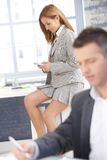 Sexy businesswoman texting in office smiling Stock Photos