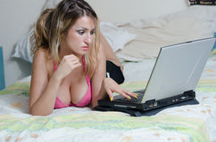 Sexy busty brunette lying on a bed with a laptop Stock Photography