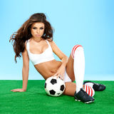Sexy busty tanned brunette with a soccer ball Stock Photos