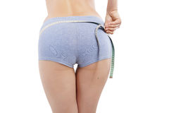 Sexy butt. Diet and detox. Girl measuring her beautiful sexy butt in panties with measure tape isolated on white background. Weight loss concept Royalty Free Stock Photos