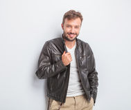 Sexy casual man holding his leather jacket's collar Royalty Free Stock Photos