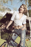 Sexy casual woman on bicycle. Portrait of pretty blonde girl with casual style wearing jeans and white shirt  posing on a bicycle in summertime Stock Photos