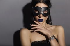 Caucasian brunette woman wearing black top, leather cat mas. K and blue lip make up. BDSM dominant theme on a neutral grey background stock image