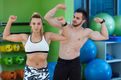 Sexy caucasian man and woman in gym couple train in fitness club with weights lifestyle wellness exercising with joy Royalty Free Stock Photos